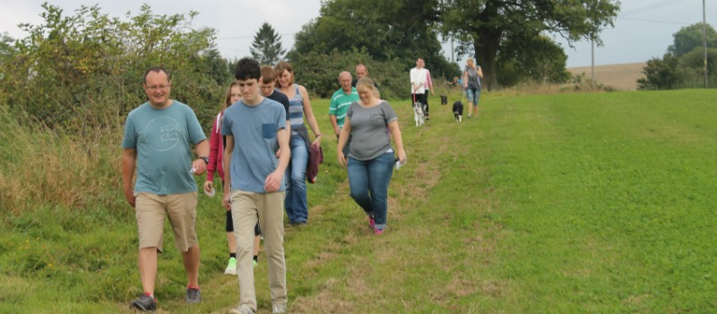 people walking through Sussex countryside