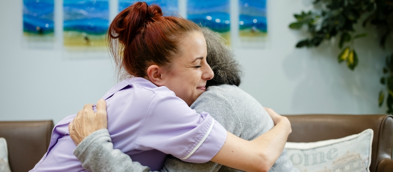 Hospice staff member and patient hugging