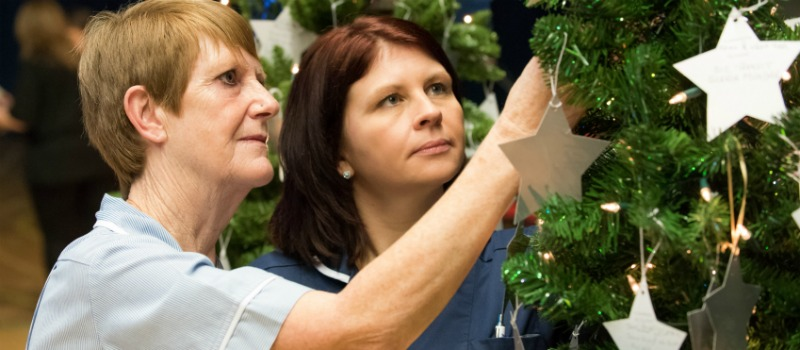 tree with hanging stars being looked at by nurses