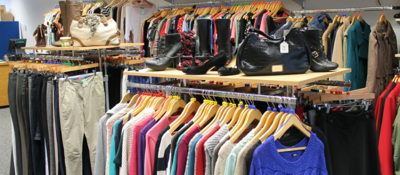 donations of clothes on hangers in charity shop