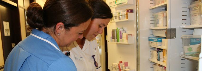 nurse and student nurse looking at drugs on a ward